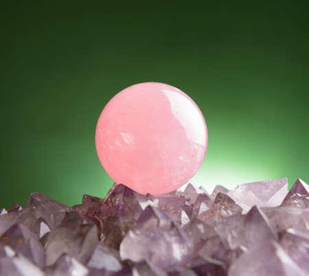 uncut: Sphere of rose quartz natural crystal on amethyst rock