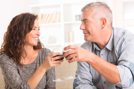 Happy couple celebrating with wine in hands in home photo