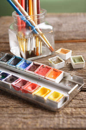Professional watercolor aquarell paints in box with brushes in jar photo