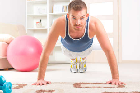 Happy attractive sporty handsome man doing push ups exercises at home photo