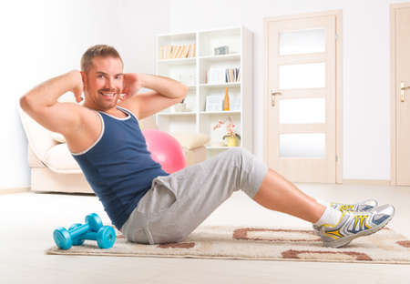 sit ups: Happy attractive sporty handsome man doing sit ups exercises at home