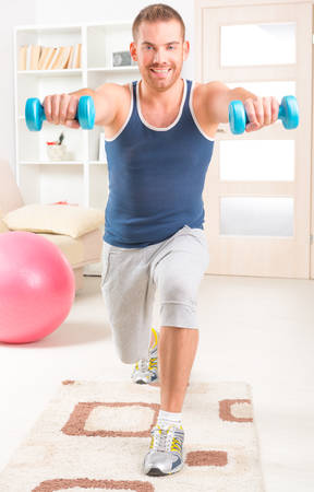 workouts: Happy attractive sporty handsome man doing workouts with dumbbells at home