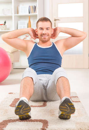 Happy attractive sporty handsome man doing sit ups exercises at home photo