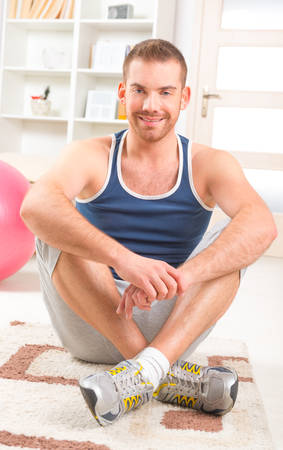 Happy attractive sporty handsome man resting after exercises at home photo