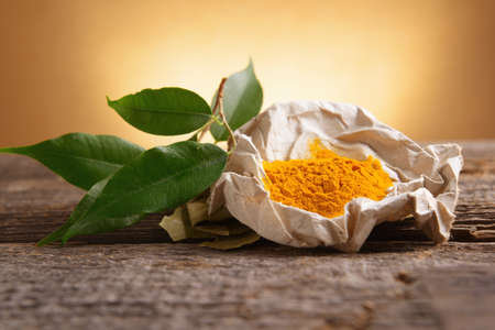 Tumeric powwder spice on wooden board with fresh leaves Stock Photo