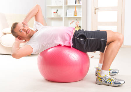 Happy attractive sporty handsome man doing sit ups exercises on the gym ball at home photo