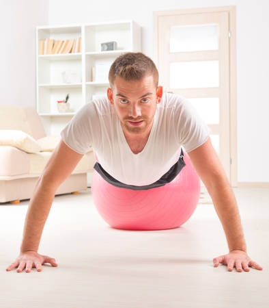Happy attractive sporty handsome man doing push ups exercises on the gym ball at home photo
