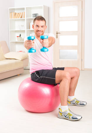 Happy attractive sporty handsome man doing workouts at home photo