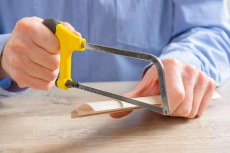 serrucho: Corte de moldeo de pl�stico con una peque�a sierra de mano en el hogar