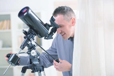 fernrohr: Mann mit astronomischen Teleskop stand in der Nähe eines Fensters
