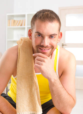 workouts: Happy attractive sporty handsome man resting after workouts with towel on the shoulder at home