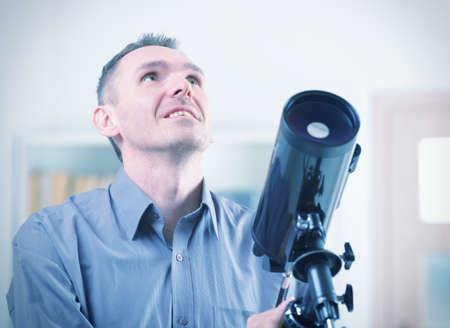 Man with astronomical telescope standing near a window  photo