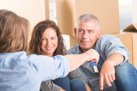 Estate agent giving keys to happy mature couple after buying new house photo