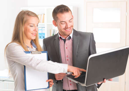 Young man and woman working together in office, looking at laptop photo