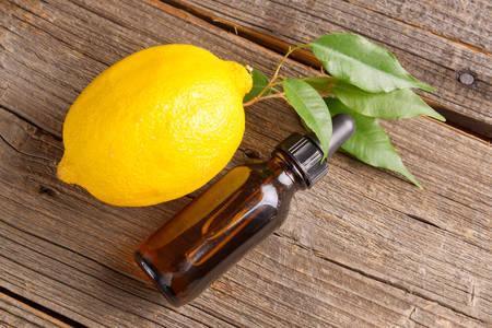 perfume oil: Bottle of essensial lemon oil with fresh organic fruit