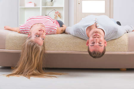 Young couple laying on the bed with heads upside down photo