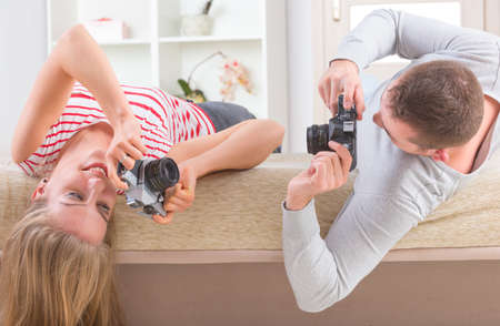 Young couple laying on the bed with heads upside down and taking pictures with old analog SLR cameras photo