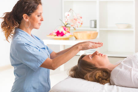 spirituality therapy: Professional Reiki healer doing reiki treatment to young woman Stock Photo