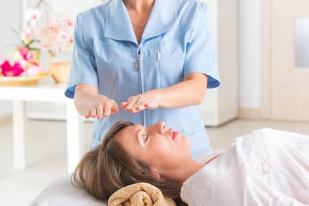 プロのレイキヒーラー若い女性にレイキの治療を行う