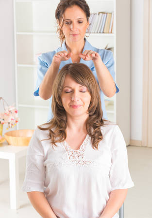 spirit healer: Professional Reiki healer doing reiki treatment to young woman Stock Photo