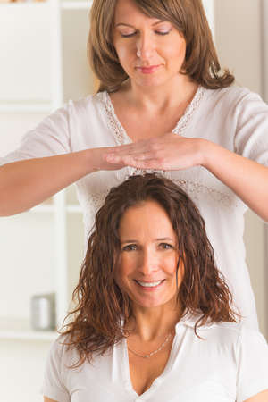 Professional Reiki healer doing reiki treatment to young woman Stock Photo - 26826117