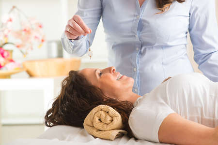 hypnosis: Alternative medicine therapist using pendulum to make a diagnosis