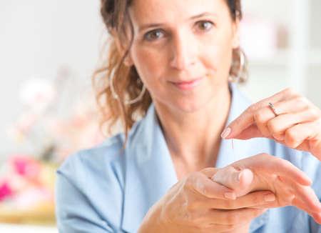 침술 치료사 그녀의 클라이언트에 침술 바늘을 적용 스톡 콘텐츠