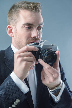 Elegant man wearing suit with bow taking photo with old style camera photo