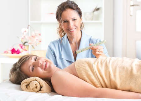 moxibustion: Alternative medicine therapist doing moxa treatment on her client Stock Photo