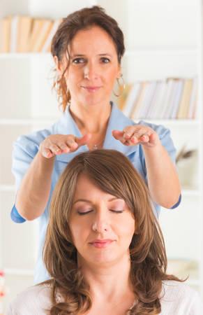 Professional Reiki healer doing reiki treatment to young woman Stock Photo
