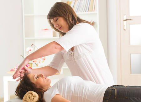 Professional Reiki healer doing reiki treatment to young woman photo