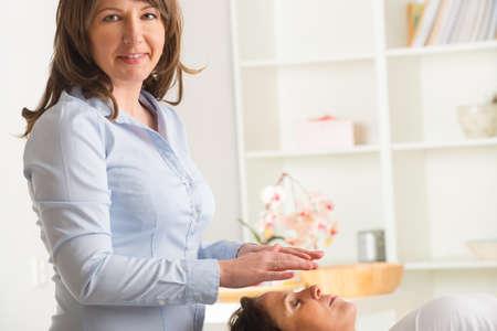 Professional Reiki healer doing reiki treatment to young woman Stock Photo - 26982850