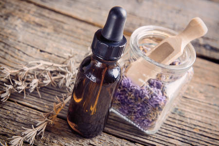 essential oils: Lavender essential oil with lavendula flowers in the jar, dry leaves of this herb near the bottle  Stock Photo