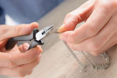 Man Reparatur oder die Erstellung von Schmuck-Silber-Kette mit einer Zange Standard-Bild