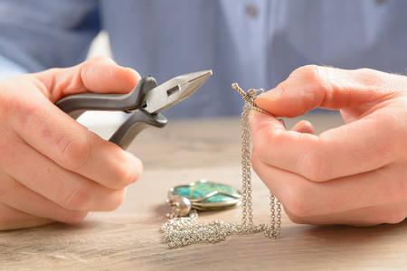 男は修復またはペンチと銀の宝石のチェーンを作成します。