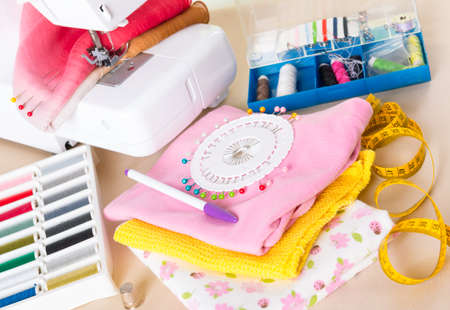 Sewing machine with colorful fabrics, threads, buttons, thimble and other sewing accesories  photo