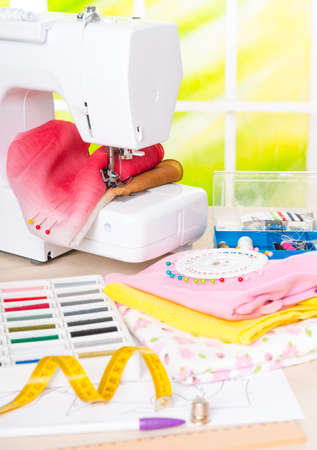 tailor measuring tape: Sewing machine with colorful fabrics, threads, buttons, thimble and other sewing accesories  Stock Photo