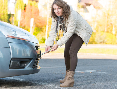 towing: Beautiful woman assembling towing hook to a broken car