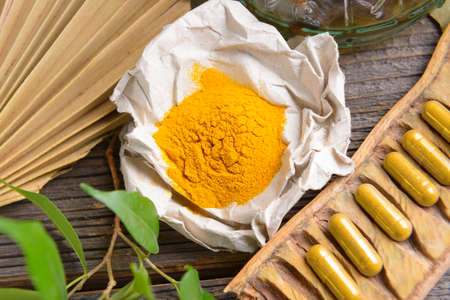 tumeric: Natural herbal tumeric capsules with fresh herb leaves and dry curcumin in paper Stock Photo