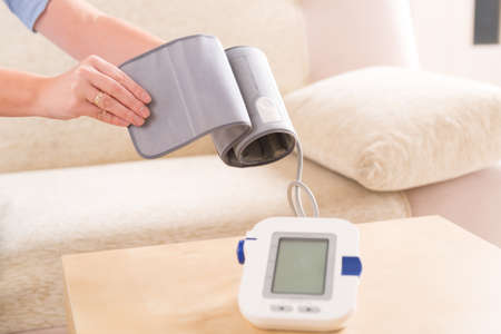 Beautiful woman checking her blood pressure at home and presenting pressure monitor cuff Stock Photo - 27358961