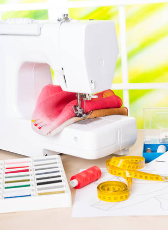 Sewing machine with colorful fabrics, threads and other sewing accesories  photo