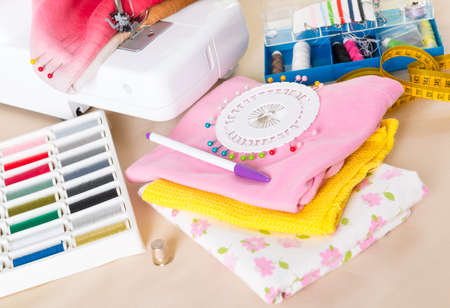 Sewing machine with colorful fabrics, threads, thimble and other sewing accesories  photo