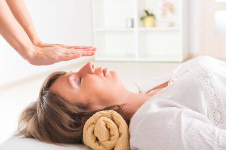 Professional Reiki healer doing reiki treatment to young woman Stock Photo