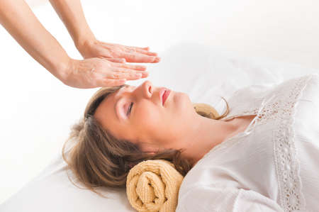 bioenergy therapy: Professional Reiki healer doing reiki treatment to young woman Stock Photo