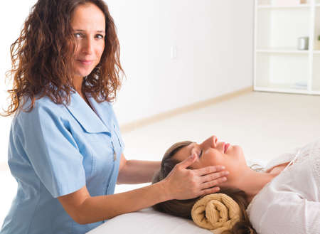 Professionelle Reiki Heiler tun Reiki Behandlung, um junge Frau