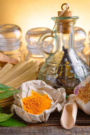 curcumin: Tumeric powder spice on wooden board with other herbs