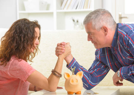 Couple doing armwrestling, concept of fighting for money Stock Photo - 27907202