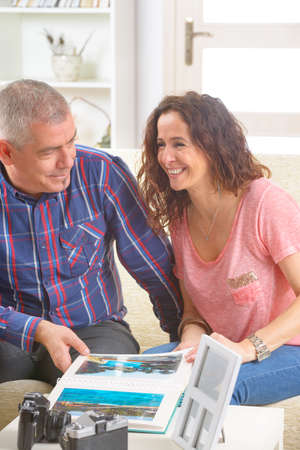 Cheerful couple looking at pictures on a photo album on the sofa at home  Stock Photo - 27907206