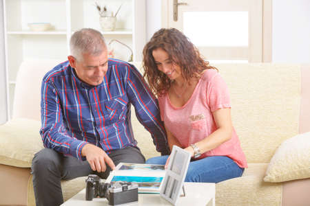 Cheerful couple looking at pictures on a photo album on the sofa at home  Stock Photo - 27907208