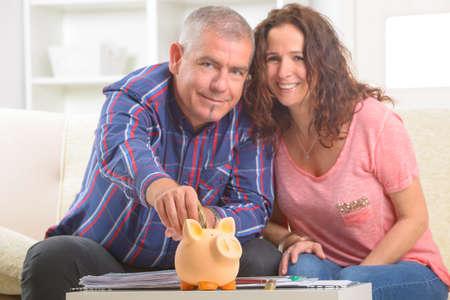 Happy couple putting money in piggybank, concept of saving Stock Photo - 27907212